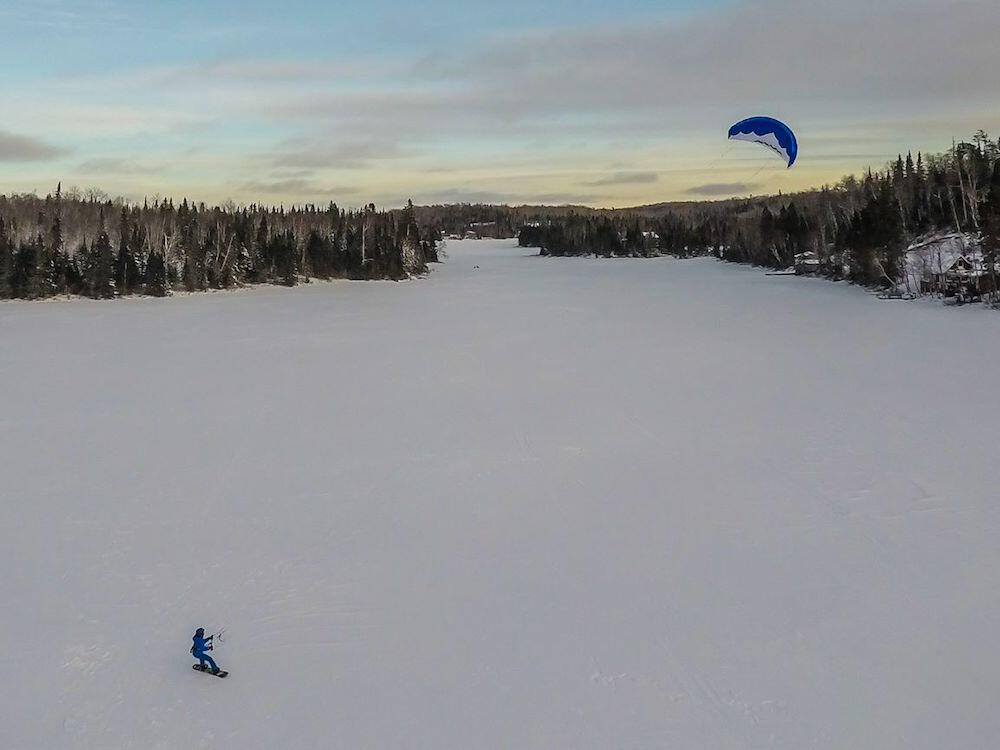 Aeral shot of person on snowboard - snowkiting on small lake