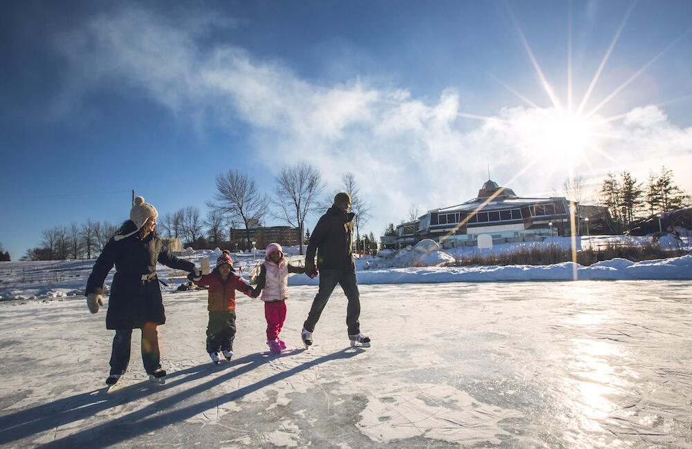 Family skating on lake in front of Science North.