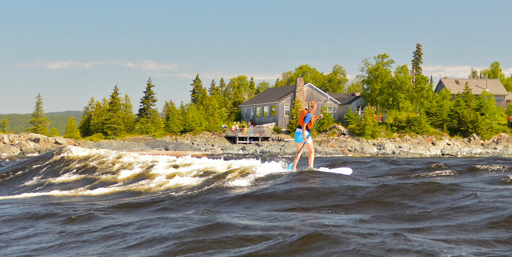 Woman on SUP board in front of small lodge on rocky point.