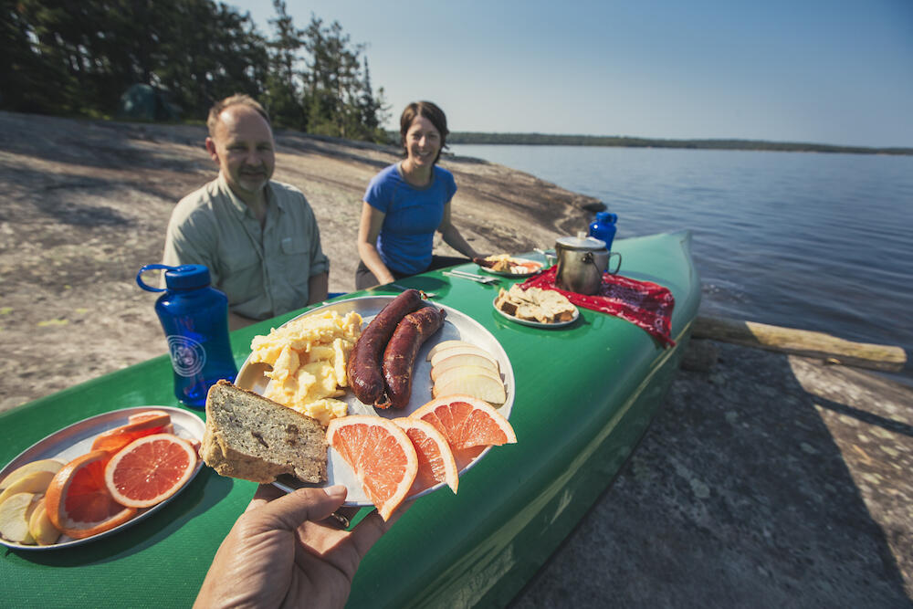 Two people sitting in front of a overturned canoe serving as a breakfast table