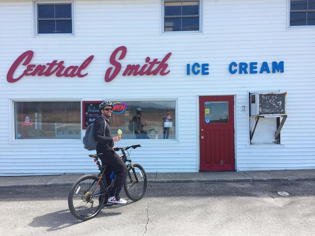 Man on a bicycle eating an ice cream in front of Central Smith Ice Cream.