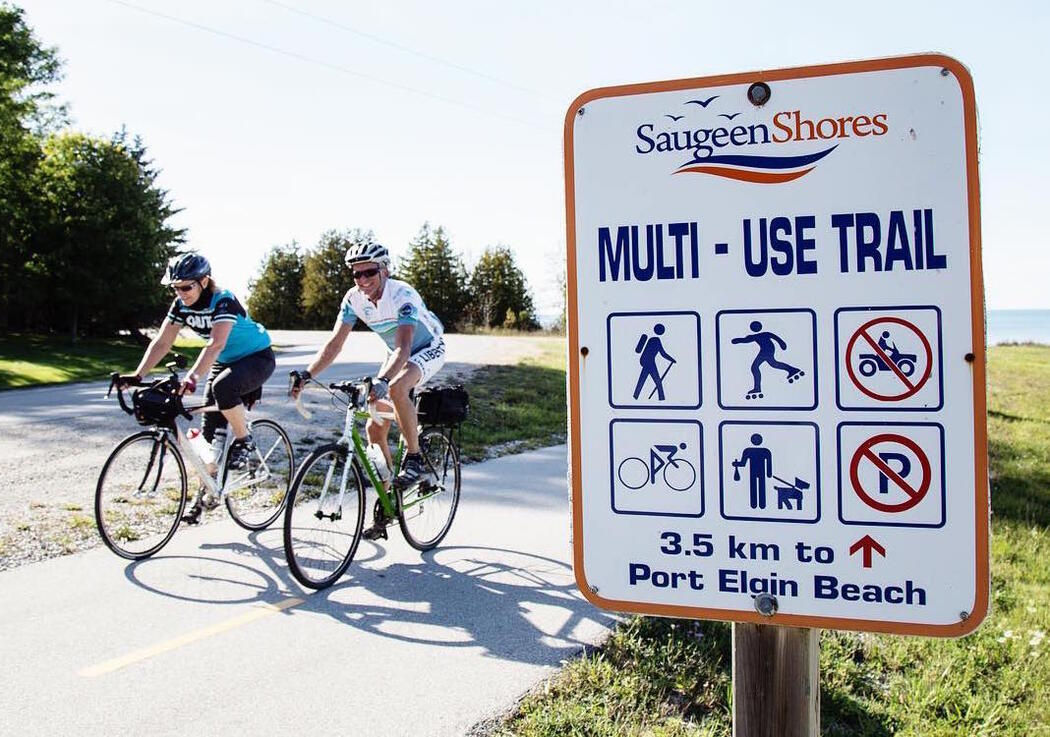 Two cyclists pedalling by Saugeen Shores Multi-Use Trail sign.