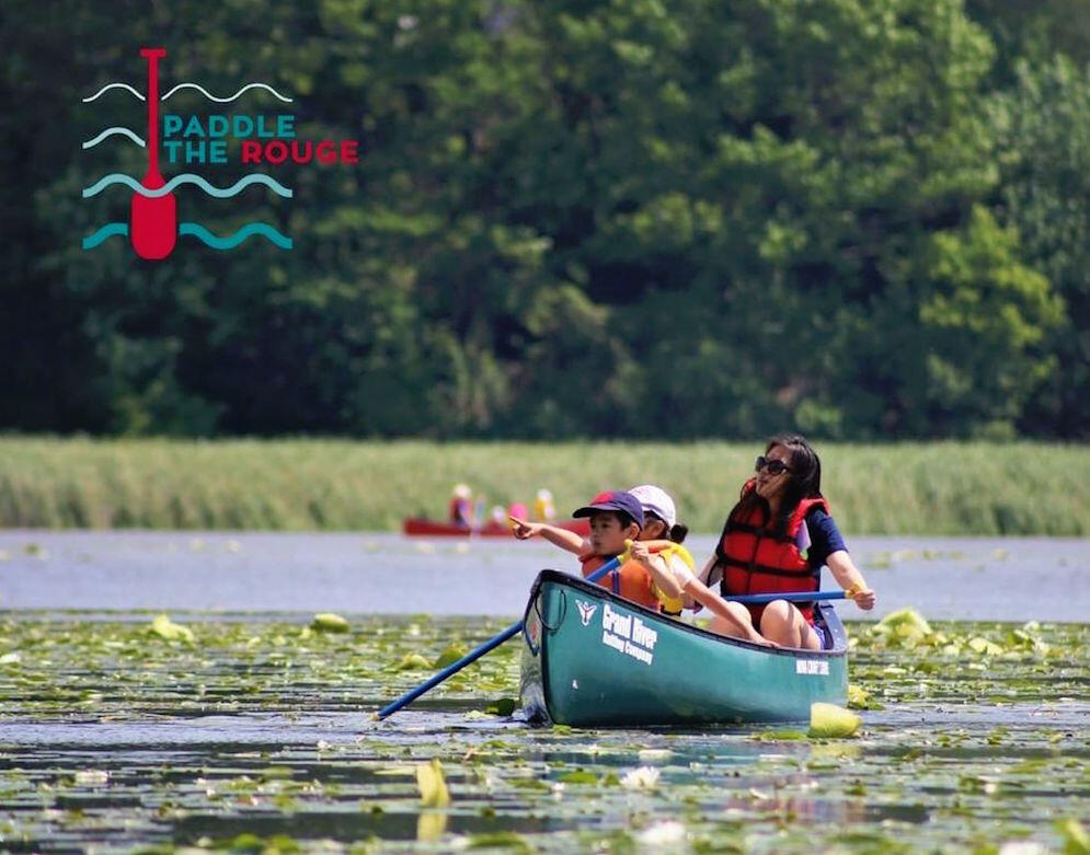Woman and two children paddling a green canoe in lily pads on Rouge River.