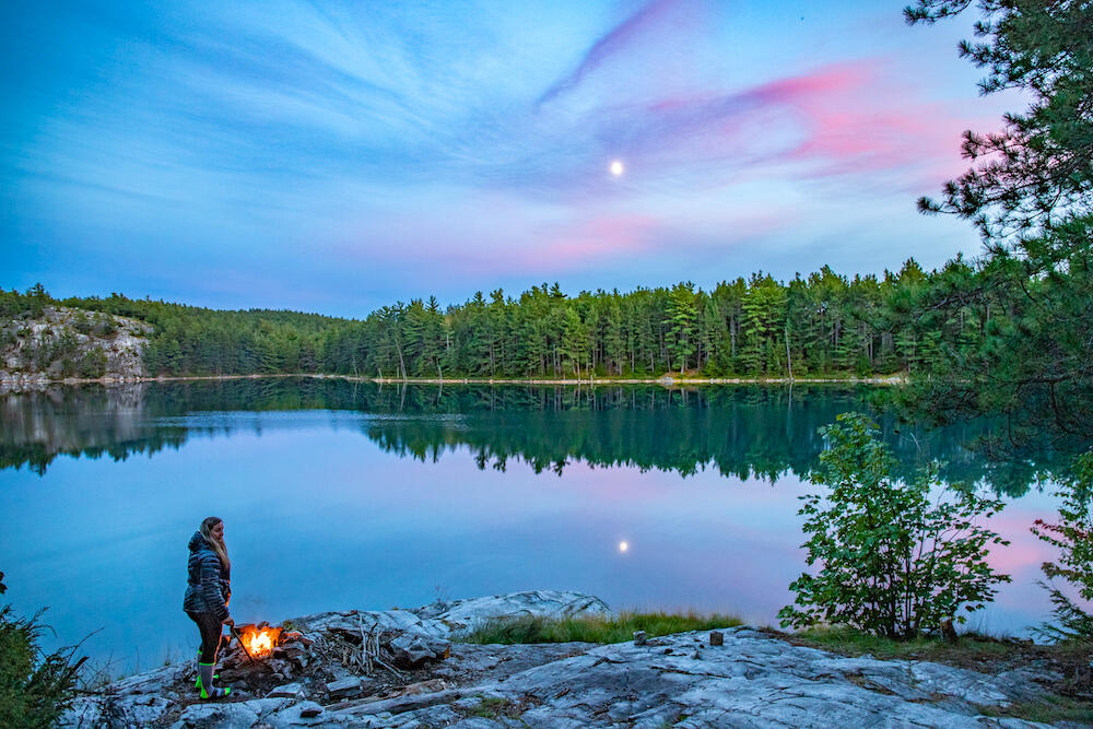 Woman standing beside a campfire looking at beautiful lake with pink swirls in sky.