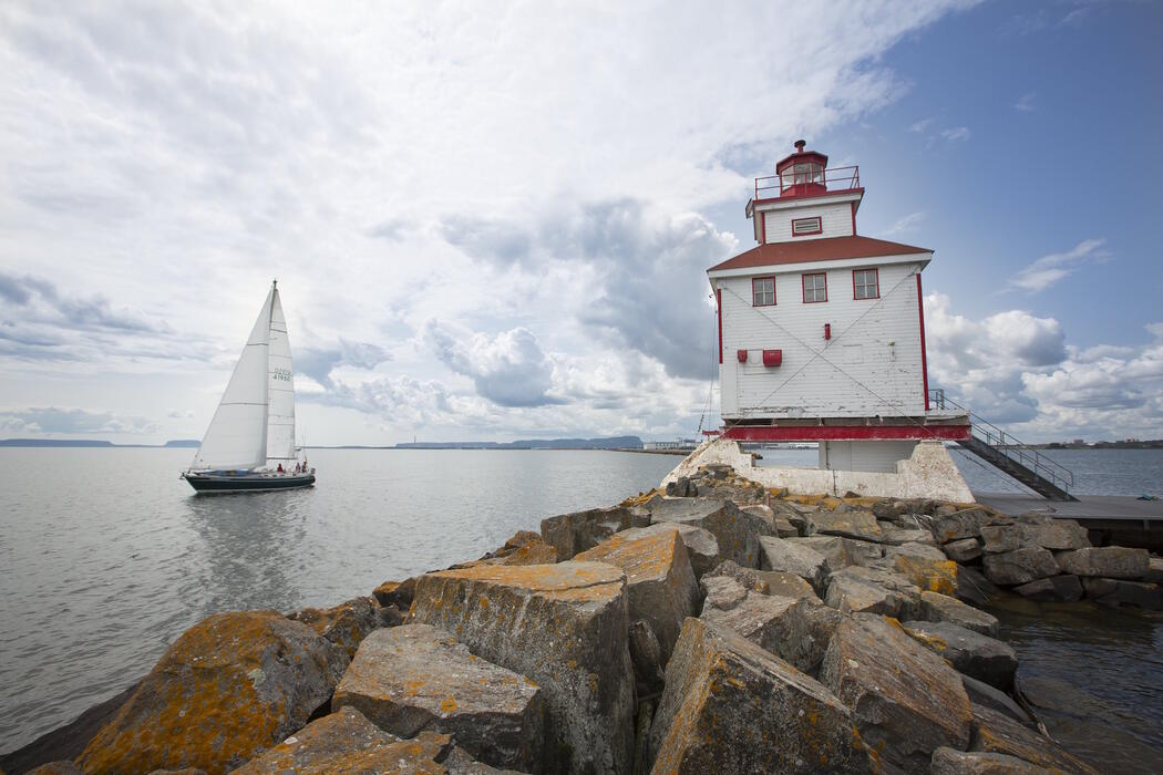 Lighthouse on rocks with a sailboat sailing by.