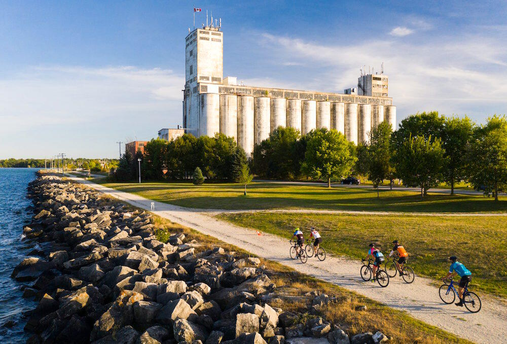 Group of cyclists riding on a road by water towards a large building.