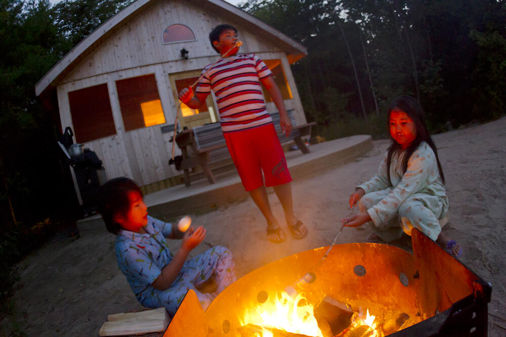 Three children roasting marshmellows over a campfire in front of a small cabin