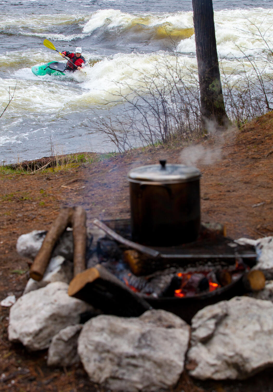 Steaming pot over campfire with a kayaker playing in whitewater in background
