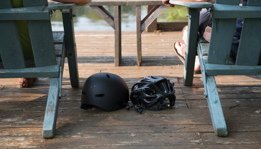 Two bicycle helmets on a deck between two wooden chairs.
