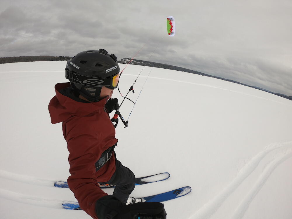 Close up of person in winter gear snowkiting.