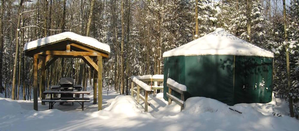 Snow covered green vinyl yurt beside a picnic table.