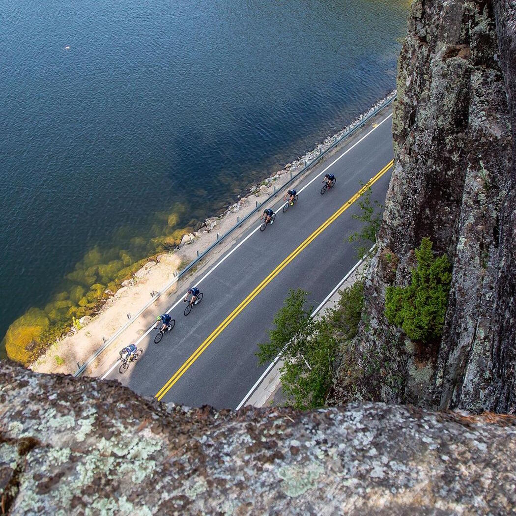 View from top of cliff looking down on cyclists on a road.