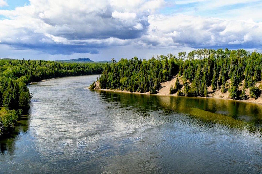 A wide calm river meandering through a beautiful Northern Ontario landscape.