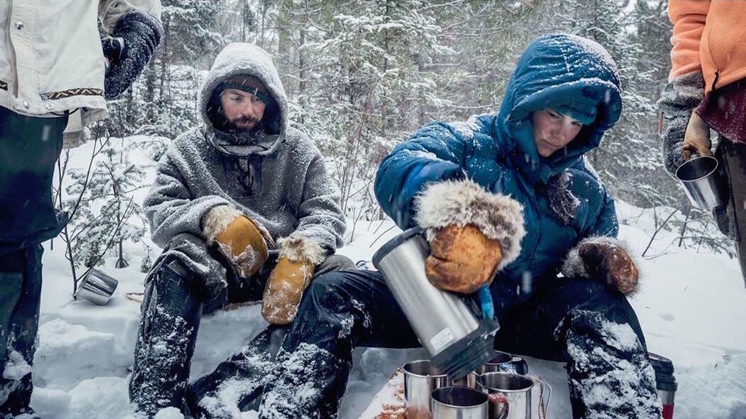 Man and woman in heavy winter clothing sitting at snowy campsite.