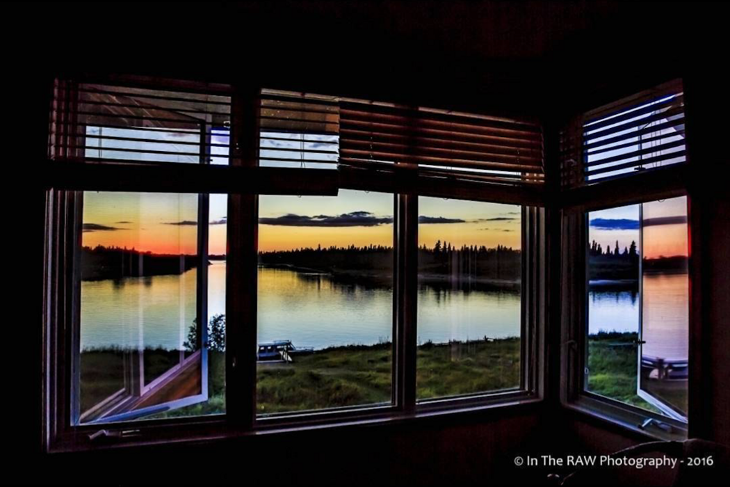 View through window of sunset over a river.