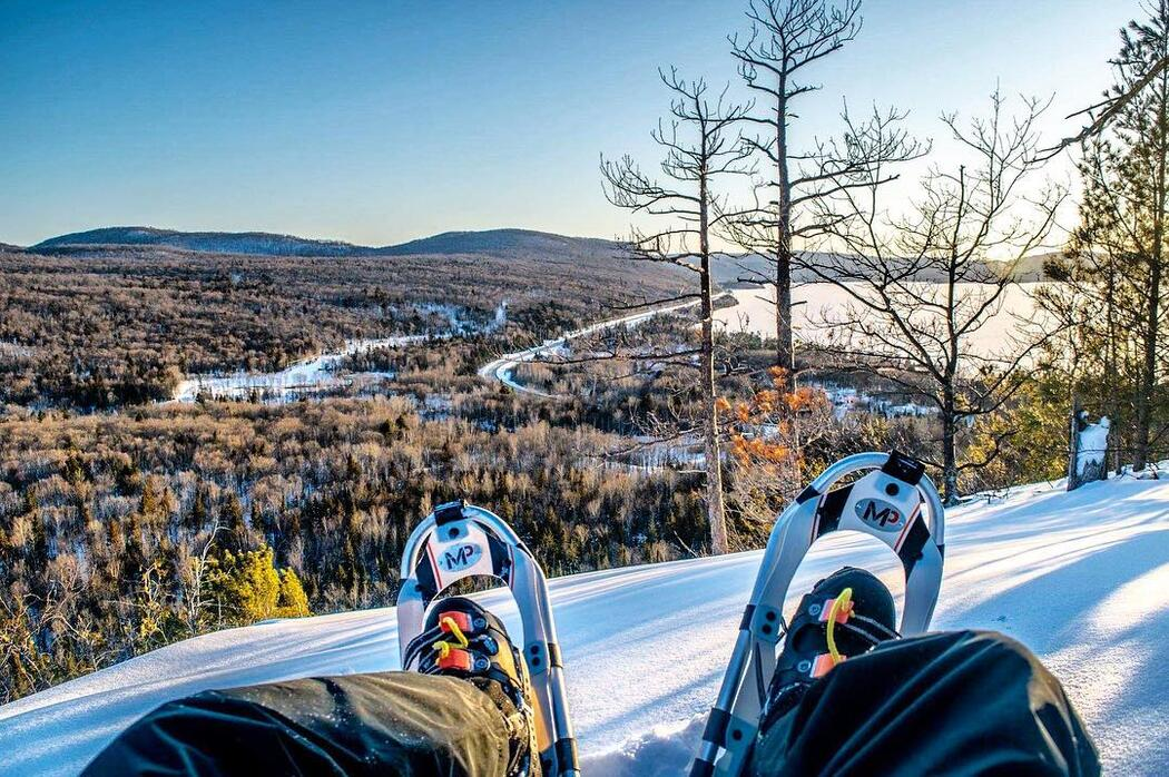 Looking down at a person's boots with snowshoes from a high vista.