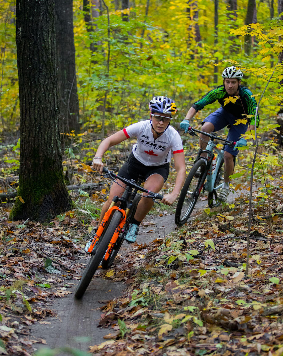Two mountain bikers on single track trail in forest