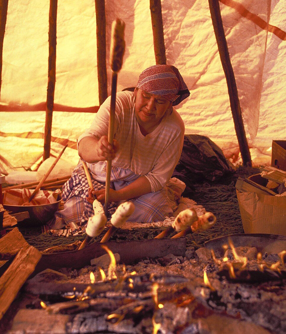 Cree woman making bannock over a fire