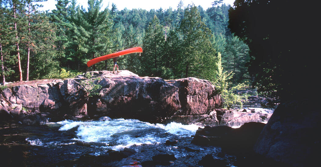 Bill Mason portaging a red canoe around rapids in Algonquin Park