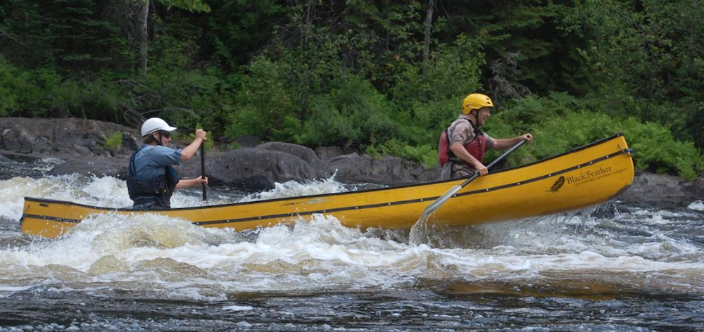 Two people in a yellow canoe in rapids.