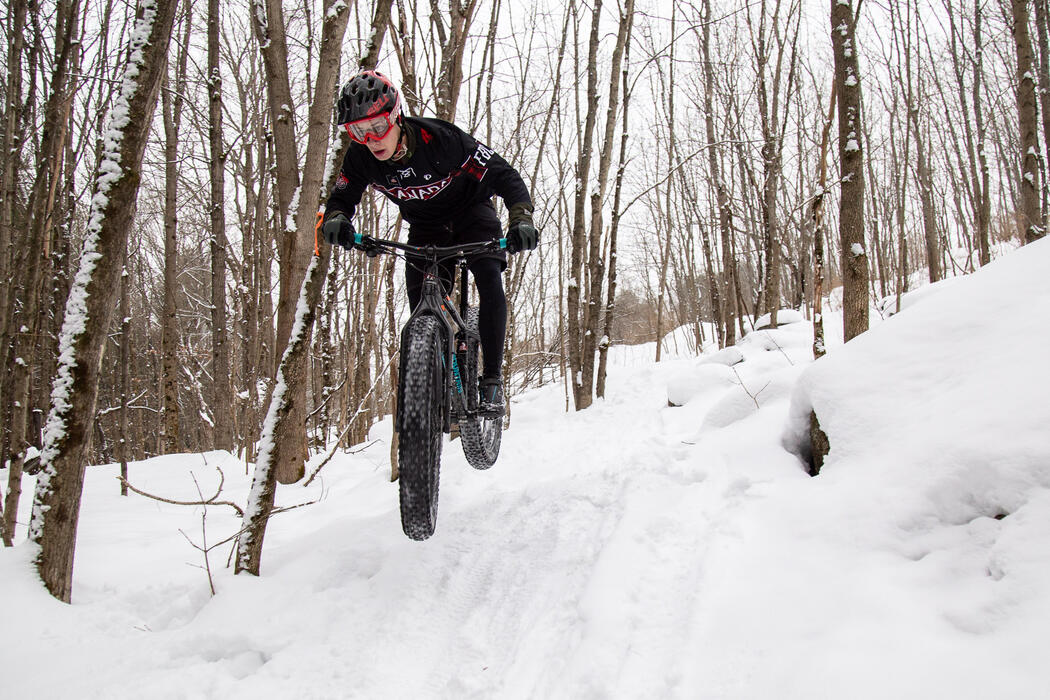 Man on fat tire mountain bike catching some air on a winter trail.