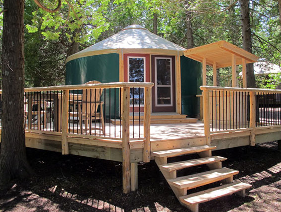 Green yurt with white roof and wooden deck
