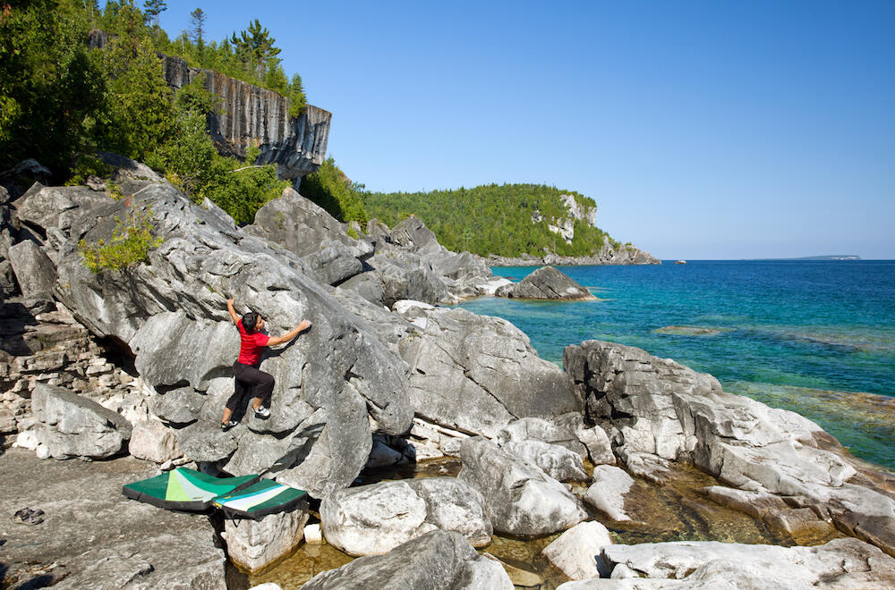 Woman climbing a boulder beside turquoise water.