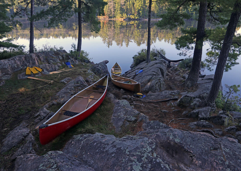 Canoes pulled up on shore next to water