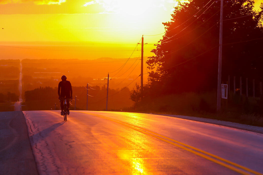 Cyclist riding into sunset on a country road.