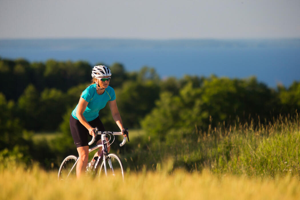 Woman cycling up a hill in summer with view of Georgian Bay.