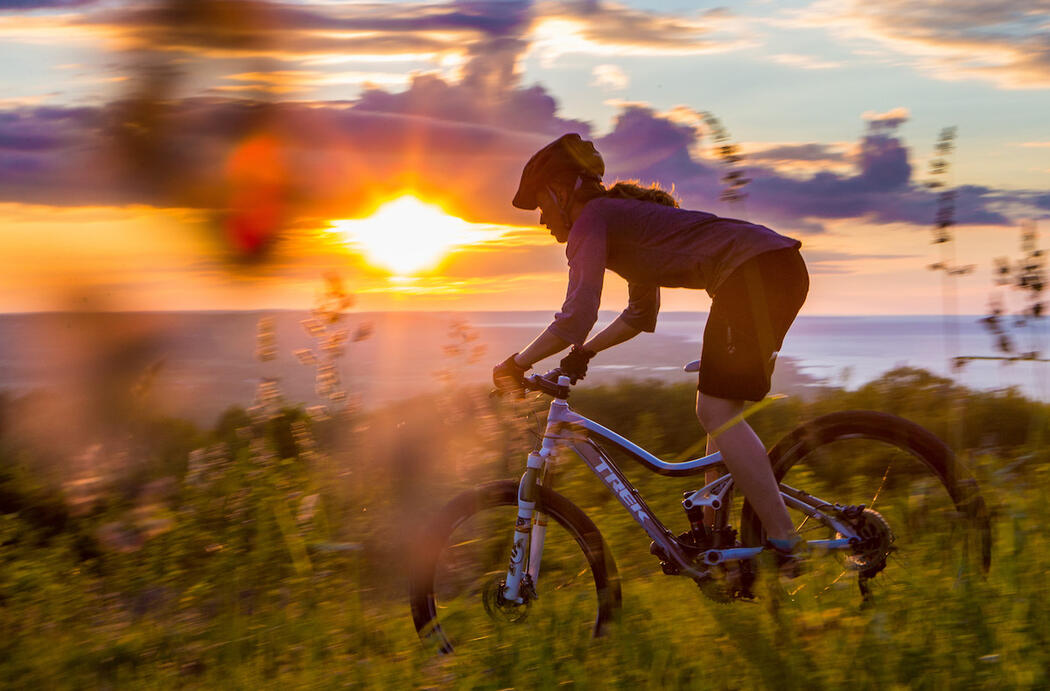 Mountain biker riding on trail with Georgian Bay and sunset in background