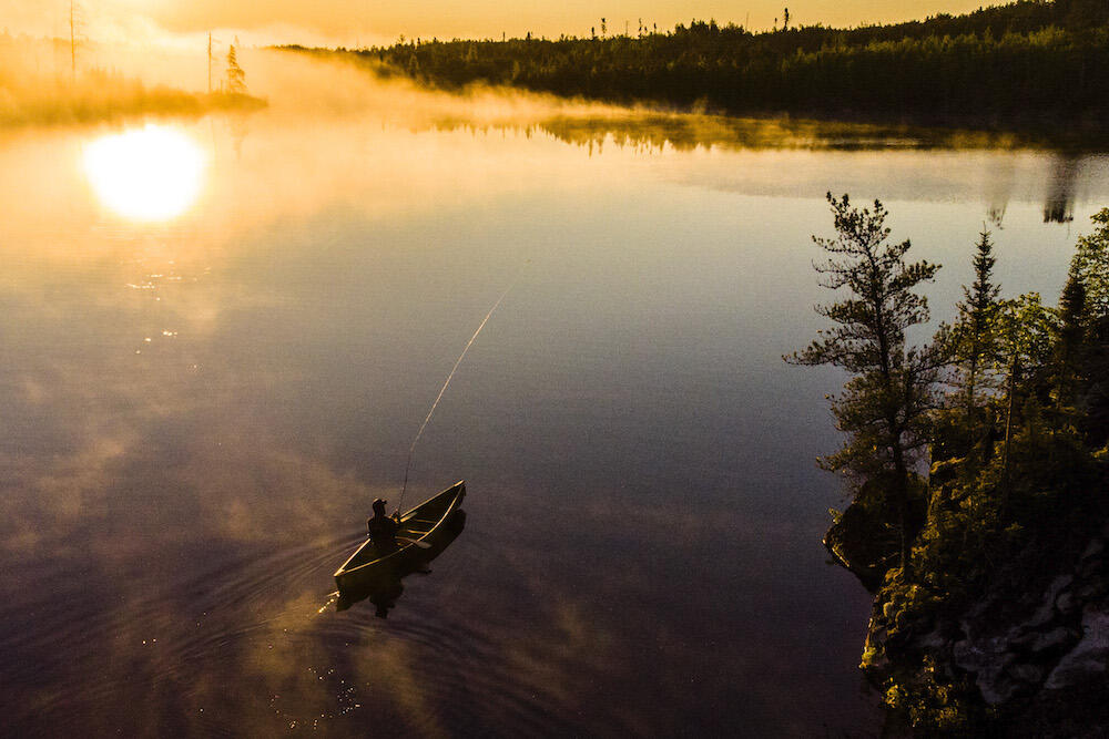 Person canoeing on lake as mist rises up