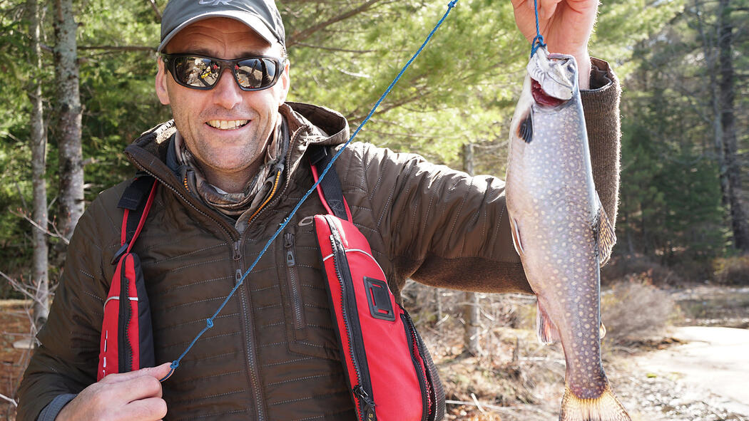 man holding a brook trout