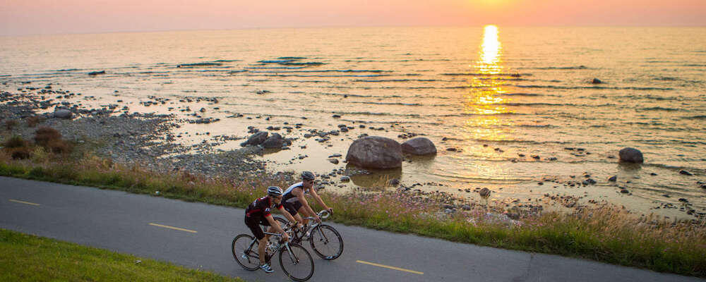 Two cyclists riding on paved trail next to water