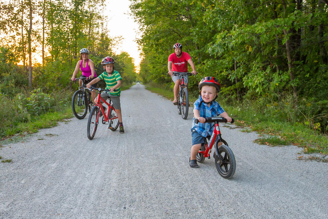 Mother, father and two young children on bicycles on rail trail.