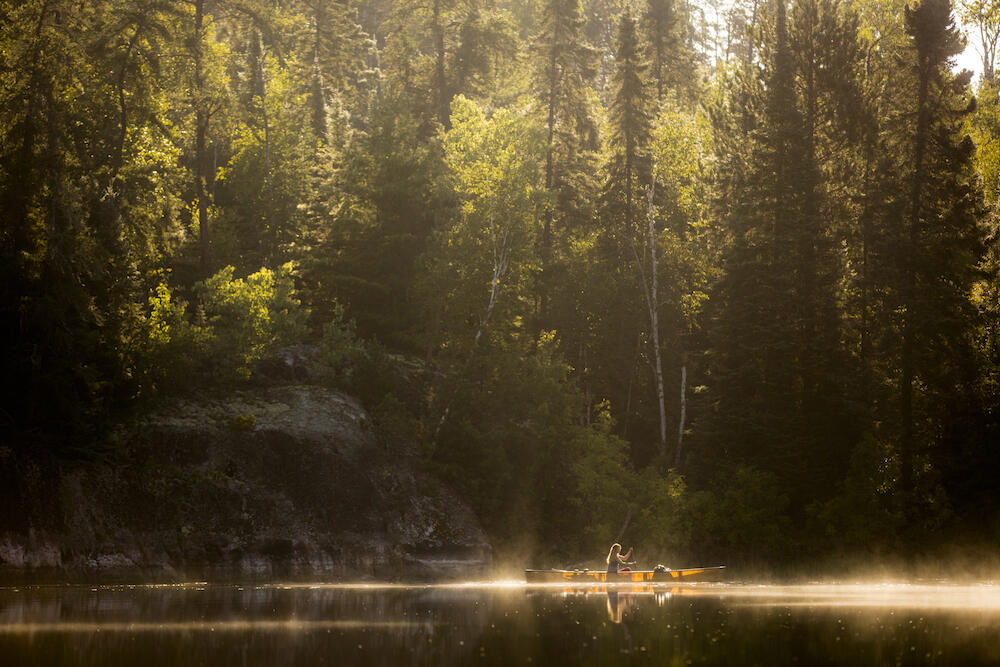 Woman in yellow canoe paddling with mist rising from water.