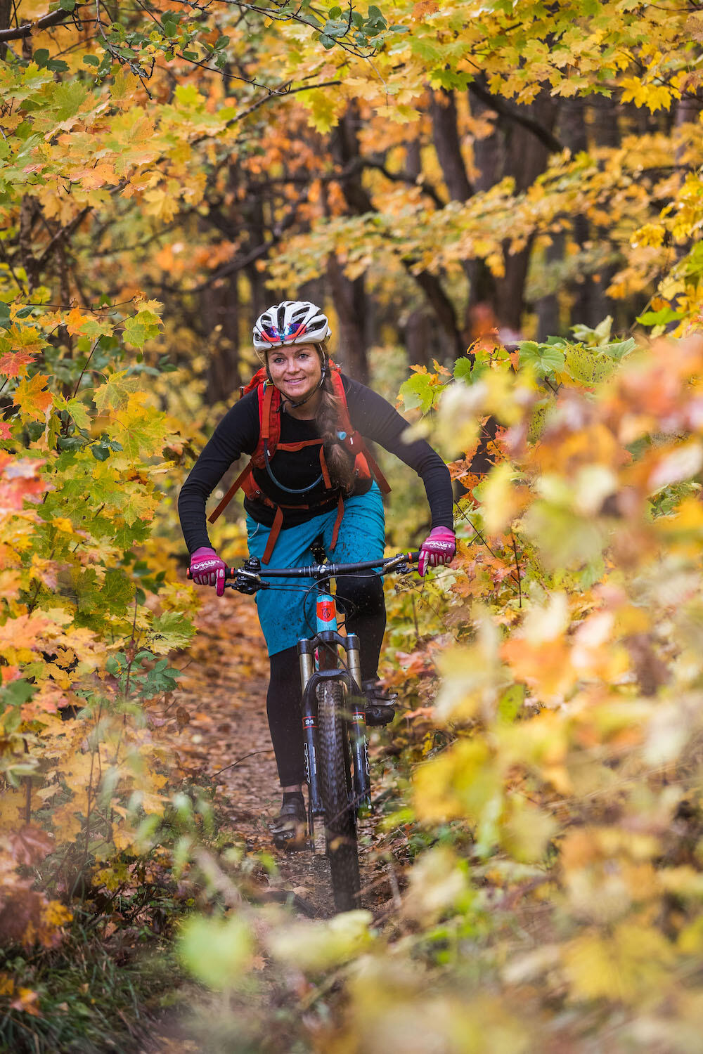 Young woman mountain biking through colourful forest