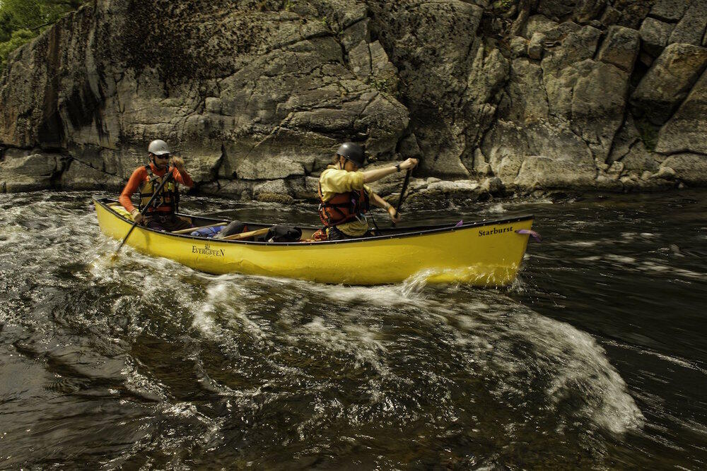 Two people in a yellow canoe paddling in rapids.