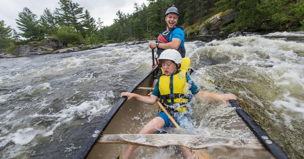 Child in mid-section of canoe with laughing guide in stern of canoe in whitewater rapids.