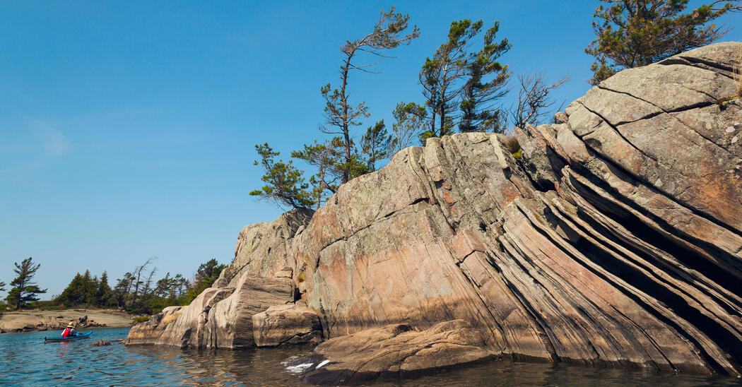 kayaker paddling by large rock island on Georgian Bay