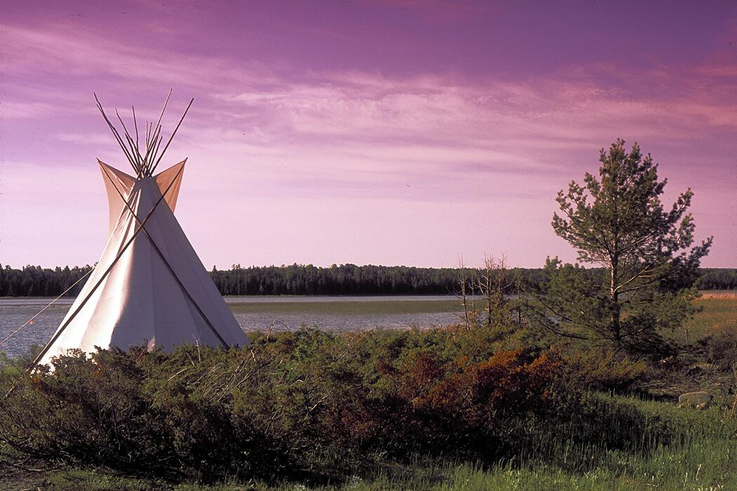 Teepee on shore of lake with sunrise in background.