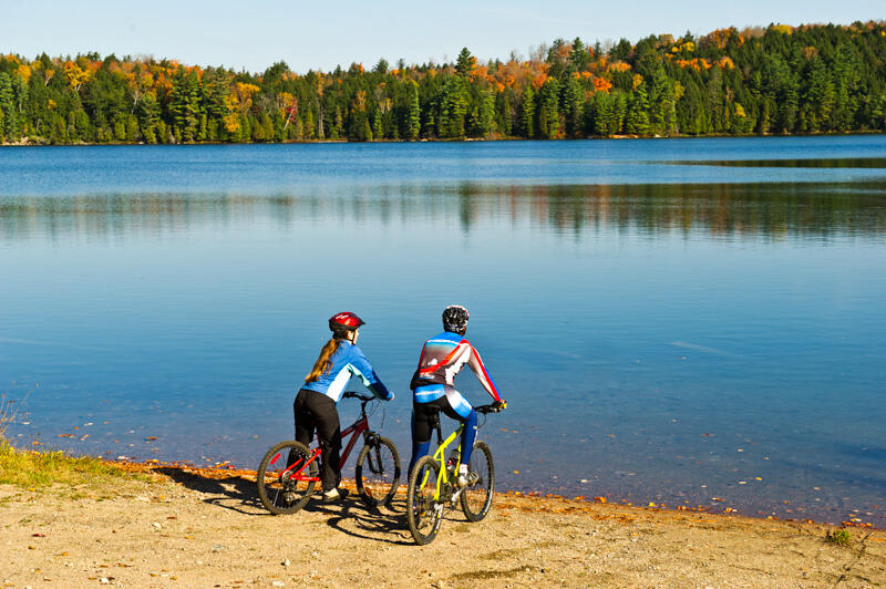 Two cyclists looking across a small lake at colourful forest.