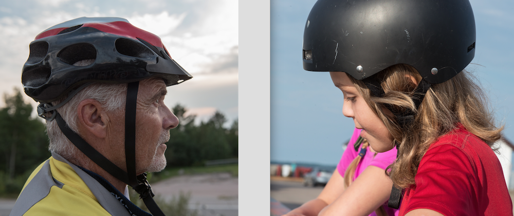 Older man and young girl wearing bike helmets.