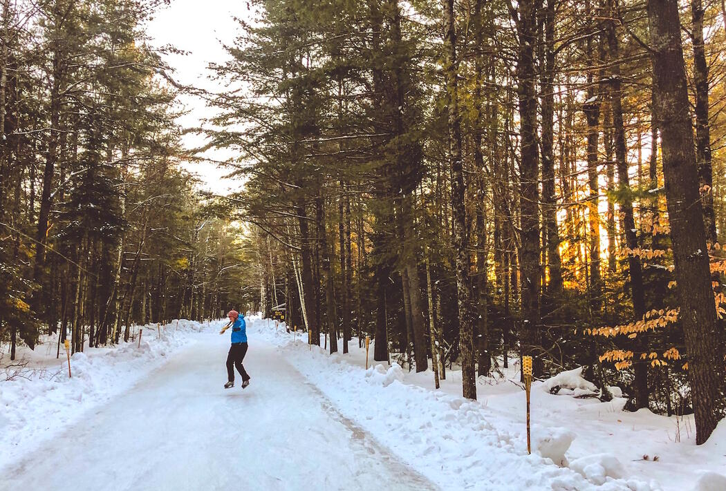 Woman skating on ice trail surrounded by tall trees