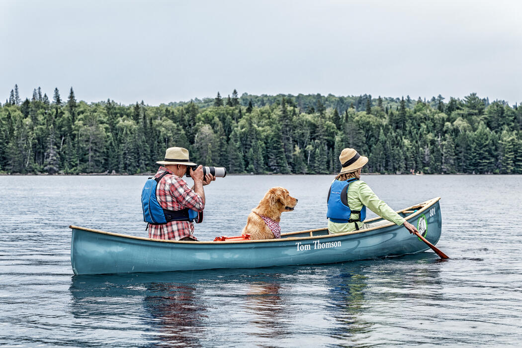 A man, woman and a dog in a Tom Thomson canoe.