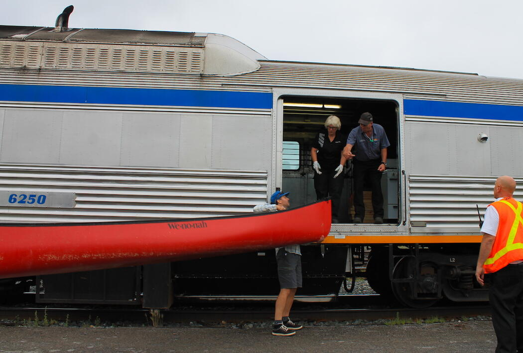 Loading red canoe onto a train