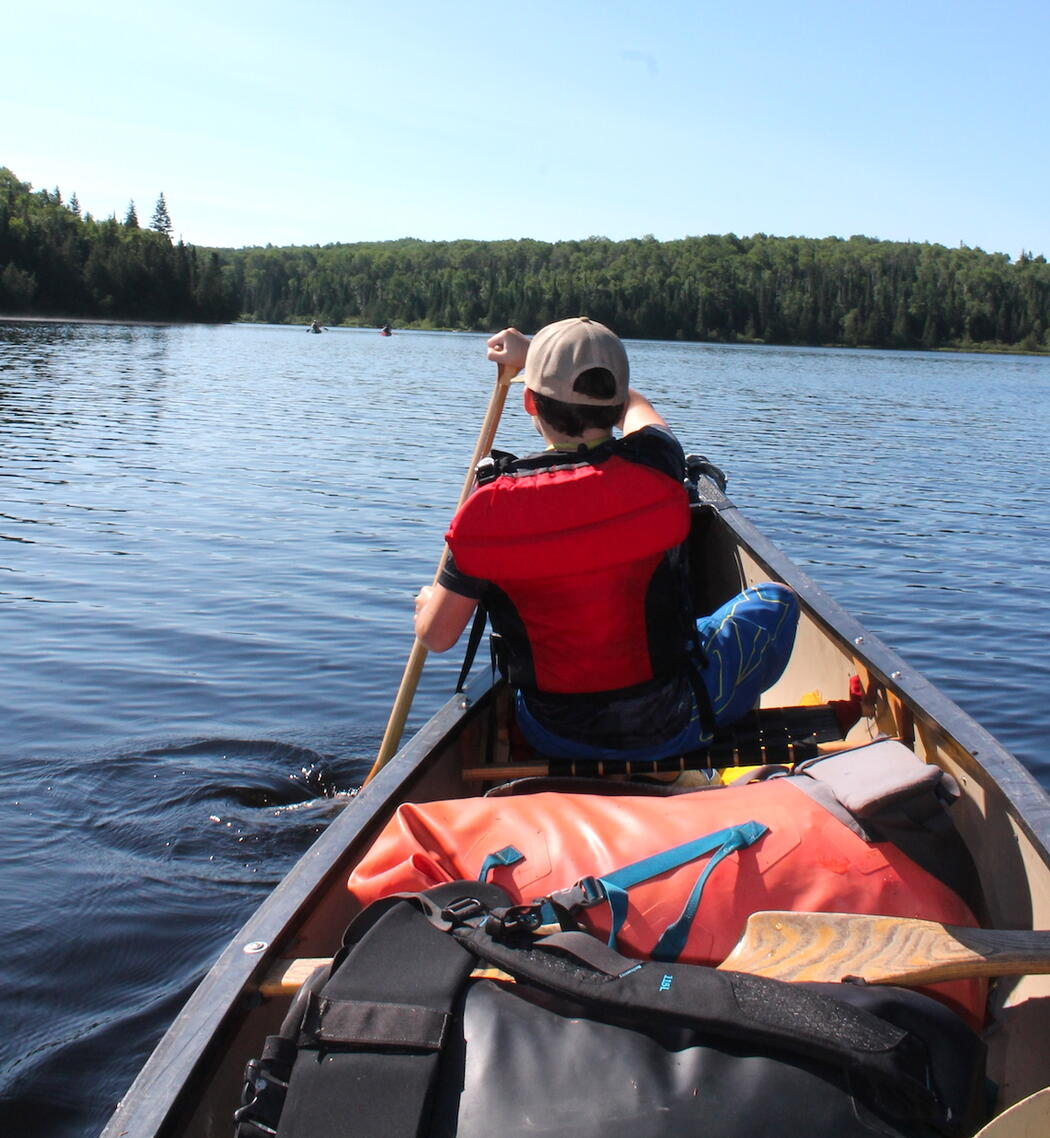 Young boy paddling in bow of canoe