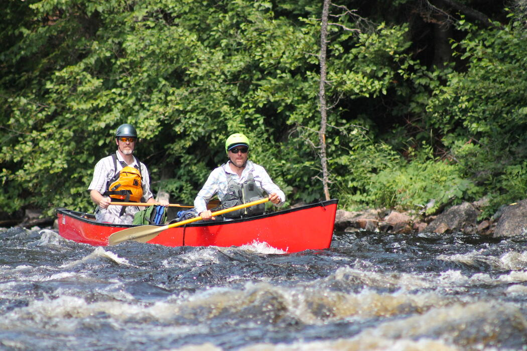 Two men in red canoe paddling on a whitewater river