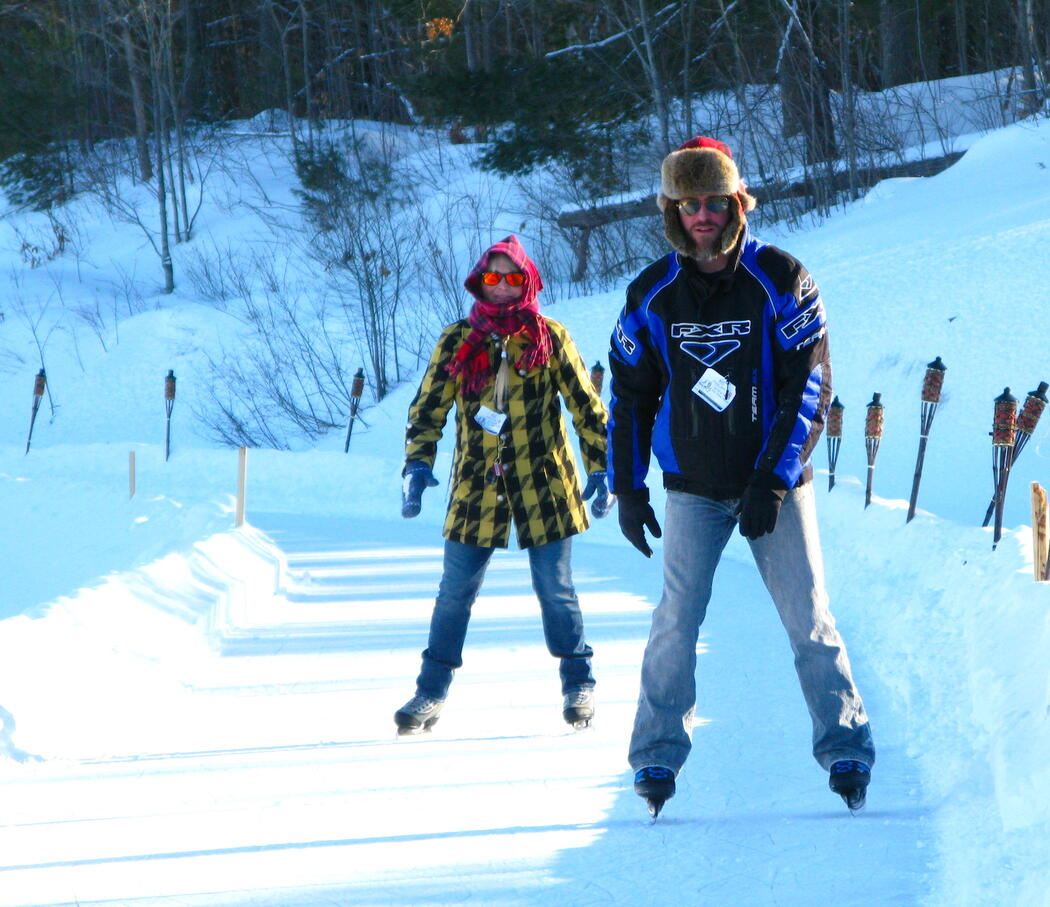 A man and a woman skating on an outdoor trail