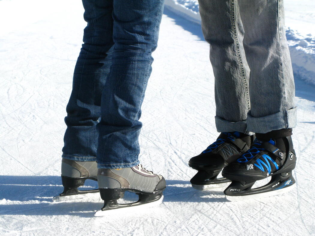 Close-up shot from knees down of a woman in skates facing a man in skates
